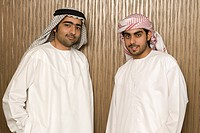 Two Arab men standing near the office wall, portrait