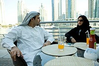 Arab couple in the restaurant at Dubai Marina, UAE