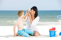 mother with son playing on beach