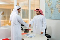 Two arab businessmen handshaking in the office