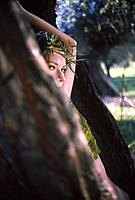 Young woman wearing crown of thorns and playing hide_and_seek in park, summer