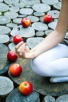 Young woman sitting in apples ring