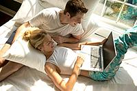 Couple Lying with Laptop in Bed