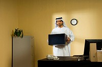 Arab man packing at office desk