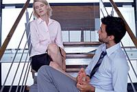 Young Businessman Touching Woman´s Feet on Stairs