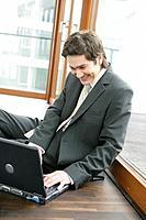 Business Man Sitting with Laptop Beside Window