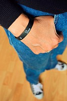 Woman in blue jeans, black sweater and sneakers, wearing a ´Lens Bracelet´ designed by Adam Elmakais - with shallow depth of field