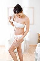 pregnant woman creaming legs