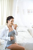 pregnant woman eating baguette