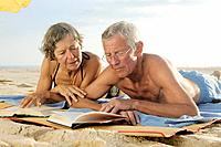 Elderly Couple Reading Books on the Beach