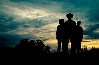 Farmer family silhouette at sunset