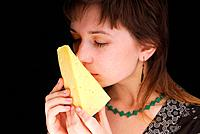 Beautiful woman smells piece of cheese