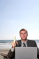 Businessman with Banana and Laptop at the Beach