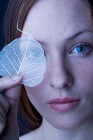 woman covering eye with leaf