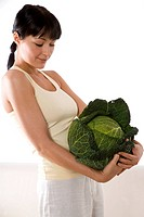 woman carrying whole green cabbage