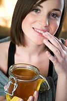 young woman putting honey into lips