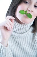 woman with mint leaf in mouth