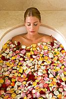 Young woman taking a bath with rose petals
