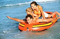 Family lying in a rubber dinghy,full shot