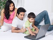 Couple using a laptop with their baby , MR779L , MR779M , MR779O