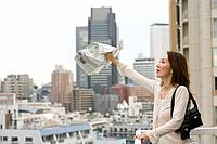 Woman Waving Newspaper on Balcony in City