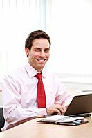 portrait of young businessman working with laptop computer
