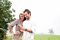 portrait of young couple reading message on mobile phone