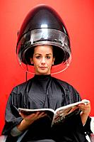 Portrait of a cute woman under a hairdressing machine while reading a magazine
