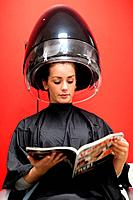 Portrait of a student under a hairdressing machine while reading a magazine