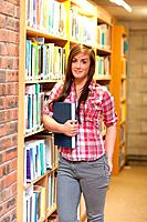 Portrait of a young student holding a book in a library