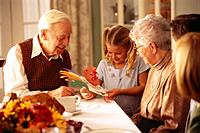 Little Girl Showing Paper Turkey to Grandparents