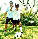Man and Boy Playing Soccer in Yard