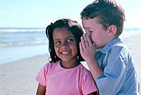 Boy Telling Girl Secret at Beach