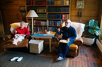 Couple in their early 70s eating and watching television Finland Europe