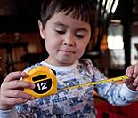 A young boy inspects his tape measure.