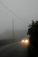 car in thick fog on country lane