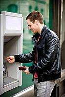A young man using a cash machine (thumbnail)