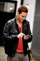 A young man standing in the street, using his mobile phone