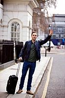 A young man with his suitcase, hailing a taxi