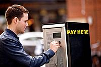 A young man putting coins in a parking meter (thumbnail)