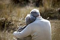 A senior couple sitting amongst the sand dunes, embracing (thumbnail)