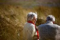 A senior couple sitting amongst the sand dunes, talking