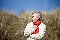 A senior woman sitting amongst the sand dunes, holding a hot drink