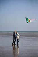 A senior couple flying a kite on the beach (thumbnail)