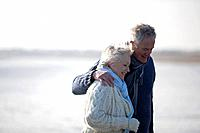 A senior couple walking along a beach, embracing
