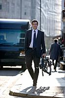 A businessman carrying his folded bicycle along the street (thumbnail)