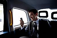 A businessman in a taxi, using his mobile phone (thumbnail)