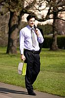A businessman walking in a park, holding a carrier bag