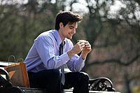 A businessman sitting on a bench, eating a sandwich