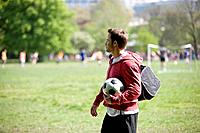 A young man standing in the park, carrying a football and a sports bag